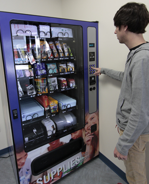 A student purchases supplies at the new Bookstore vending machine (photo by Josh Balduf).