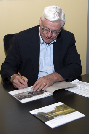 Dr. James Crooks signs a copy of his book in the Lufrano Interculture Gallery in the Student Union (photo by Richard Anderson).