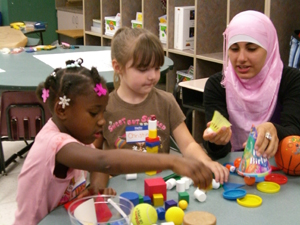 UNF elementary education undergraduate student Nura David works with two kindergarten children learning three-dimensional shapes during the ABC Literacy: Arts, Books, Community TLO at Woodland Acres  Elementary Professional Development School.