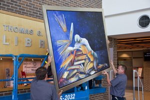 "University workers install ""The Flight of Wisdom"" by artist Susanne Schuenke in the main lobby of the Thomas Carpenter Library. More than 80 pieces of art are on display as part of the Art in the Library program."