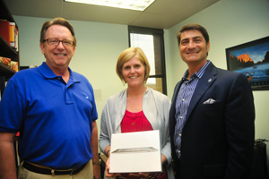 President John Delaney and United Way committee chair Philip Green surprised Nutrition and Dietetics instructor Jennifer Ross with a new iPad. Ross won the United Way campaign's random drawing. (Photo by Dennis Ho)