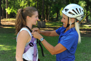 Amy Costa helps a student get strapped in to a harness at UNFs new Osprey Challenge Course