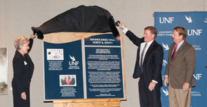 Mary Virginia Skinner (left) is assisted by Board of Trustees member Myron Pincomb (right) in unveiling the memorial plaque that will adorn the newly named Skinner-Jones Hall Buildings. President John A. Delaney (far right) spoke during the dedication ceremony (Photo by Jennifer Grissom).