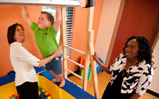 Jennifer Ancelin help her son Arik with his motor skills at Hope Haven, while Dr. Patterson observes.