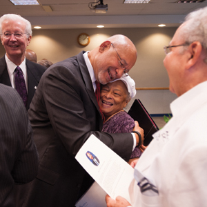 Dr. Adam W. Herbert stops to accept a hug after the dedication ceremony in his honor.