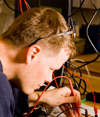 Engineering student using wired testing equipment