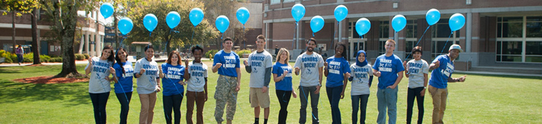 Honors students pose on The Green holding blue balloons