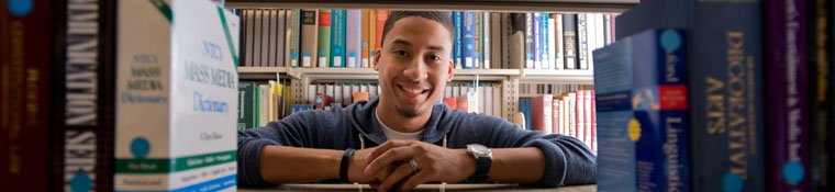 Student smiles amid library bookshelves