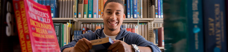 Student smiles through shelves of books