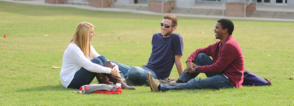 Three students sitting and talking on the lawn