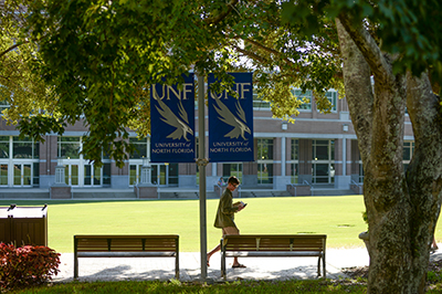 Student walking by banners on campus