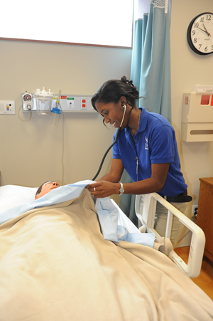 Chelsea Laguerre practices on a test dummy located in the Brooks College of Health (Photo by Jennifer Grissom).