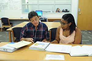 An instructor assists a student with her accounting homework (photo by Jennifer Grissom)