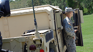 A photo of a student member of UNF's ROTC squad standing next to a humvee (Photo by Jennifer Grissom)