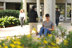 A student enjoys some study time outside on UNF's environmentally beautiful campus (photo by Jennifer Grissom).