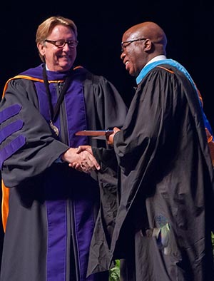 President John A. Delaney shakes hands with award recipient Oupa Seane