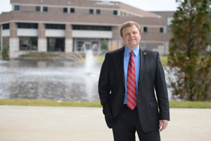 Dr. Kostin in front of the Coggin College of Business.