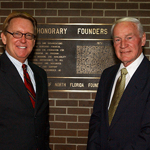 A photo of President John A. Delaney (left) standing with founding UNF President Thomas G. Carpenter