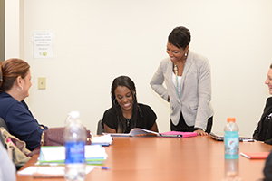Dr. JeffriAnne Wilder works with a group of students in a class
