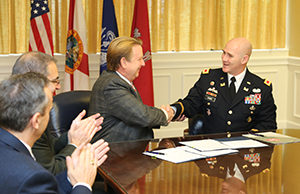 A photo of President John A. Delaney shaking hands with Col. Alan Dodd of the U.S Army Corps of Engineers