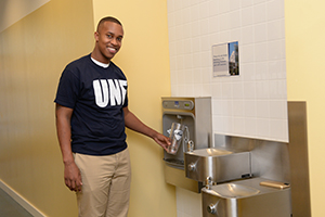 A student using a hydration station to refill a bottle