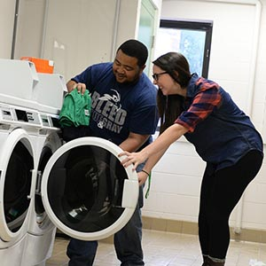 Student using the washing and dryers at a residence hall