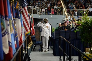 A service member salutes the flag during a recent UNF graduation