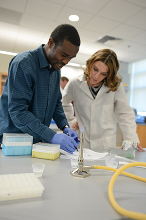 A student working with a professor in a lab