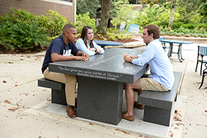 Three students in the middle of a discussion while they sit at Thoreau's Table