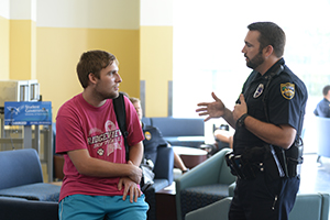 UNF police officer talks with student at the Coffee with a Cop event