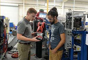UNF alum and Stenner Pump employee Jesse Rochelle on left talks with UNF engineering student Michael Otero as they look at robot's mechanisms