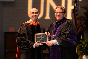 UNF's Juan Aceros poses with President Delaney to accept faculty award