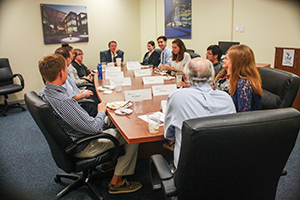 Group of UNF Hicks Honors students seated around table with President John A. Delaney