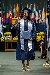 UNF graduate in cap and gown holds diploma