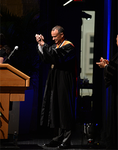 Distinguished professor Dominik Güss speaks at podium before Convocation ceremony audience