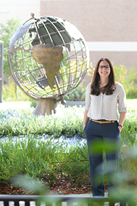 Ruth Lopez director of International Center stands by globe on campus for photo