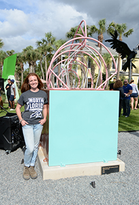 Student stands next to her sculpture on display in seaside park