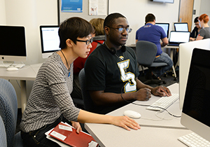 An instructor and student in the UNF computer lab