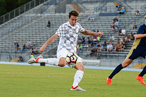 UNF's Milan Kovacs kicking soccer ball on the field