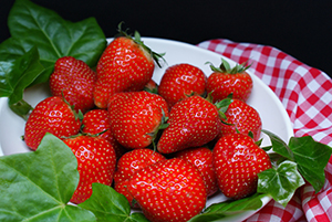 Plate filled with red, ripe whole strawberries