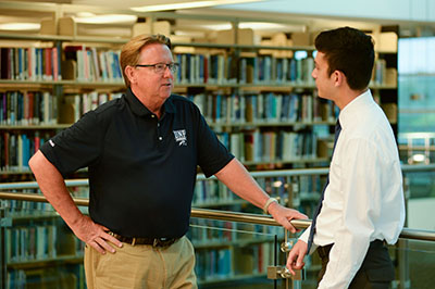 President Delaney talks to student in Library