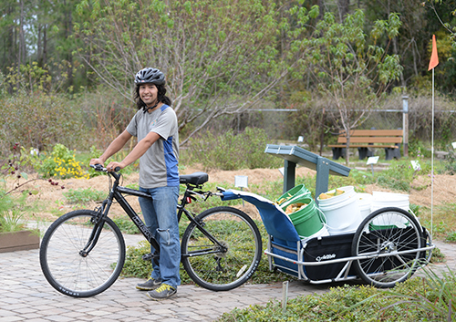 UNF student Paul Diaz on bike with trailer attached
