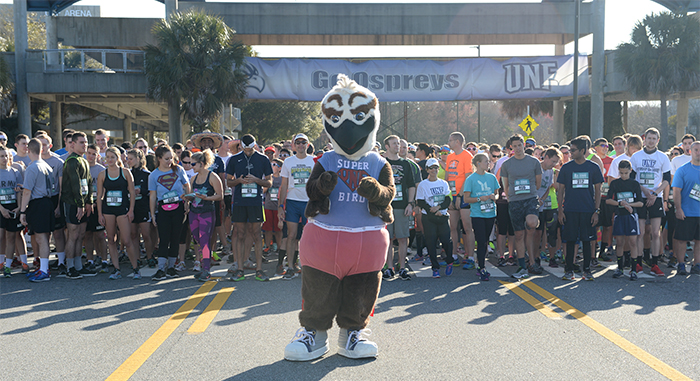 Ozzie the Osprey and runners stand at the starting line