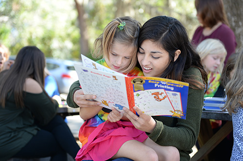 UNF student working on reading project with child
