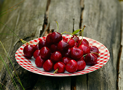 Bowl of red cherries on table