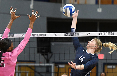 UNF volleyball player hitting near the net