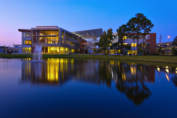 Student Union lights shine on the water as the sun sets