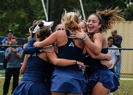 Women's tennis team in huddle to celebrate win