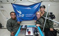 Members of the Orbital Ospreys team hold up a UNF flag above