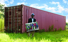 Ebenson Verdule near a container that will be converted into a dorm for students in Haiti